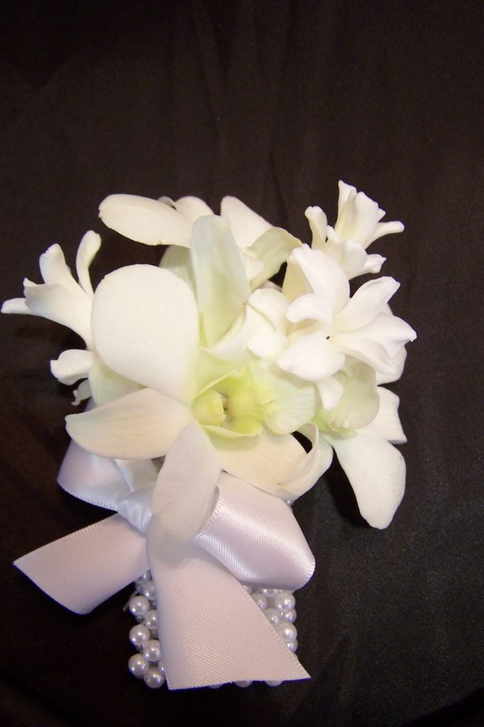 #11 White pearl elaticized bracelet with 3 Hyacinth floret sprays and 3 Singapore Orchid flowers. Finished with white satin ribbon. $60.00