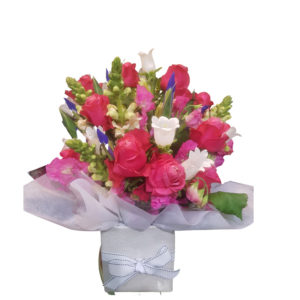A bouquet of seasonal flowers placed in a container and gift wrapped box